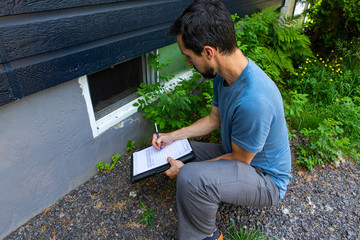 Indoor damp & air quality (IAQ) testing. A close up view on environmental home quality inspector at work, filling in a form as he inspects the exterior of a cellar window, with room for copy.