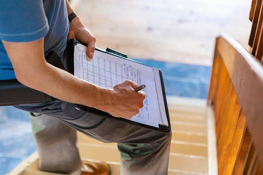 Indoor damp & air quality (IAQ) testing. A close up and high angle view of a professional male wearing blue t-shirt, writing out forms during a home inspection, standing on stairs with copy-space.