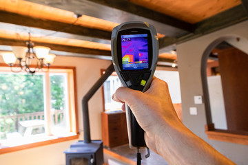 Indoor damp & air quality (IAQ) testing. A first person perspective holding an infrared thermal vision device, showing heat sources and cold spots inside a family room with copy space.