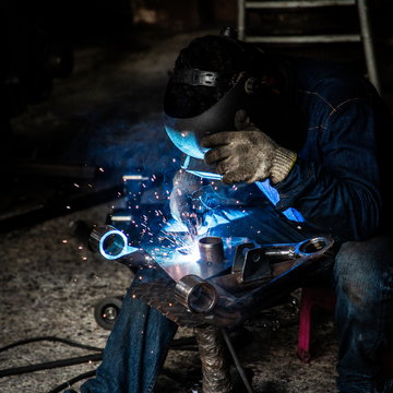 professional welder man working in protect uniform and helmet in industrial factory ,  manufacture linking and repair concept square background .
