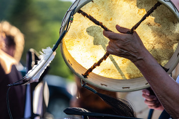 Sacred drums during spiritual singing. A traditionally constructed native drum is seen in the hands of a spiritual person with a sacred eagle feather during a park gig celebrating traditional music