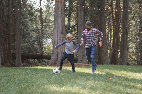 father and son playing soccer near the woods