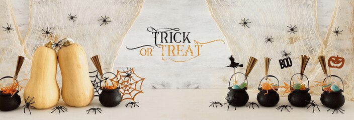 holidays image of Halloween. Pumpkins, witcher cauldron, broom, treats over white wooden table