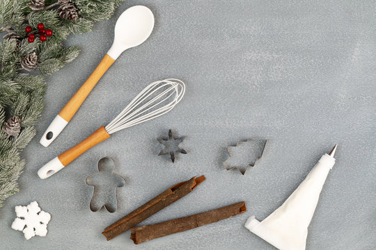 Utensils for Christmas baking with spoon, whisk, icing piping bag, cookie cutters, cinnamon sticks and snow flake with snowy fir branches with cones over stone like background with copy space flat lay
