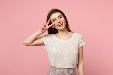 Laughing young woman in casual light clothes posing isolated on pastel pink wall background, studio portrait. People sincere emotions lifestyle concept. Mock up copy space. Showing victory sign.