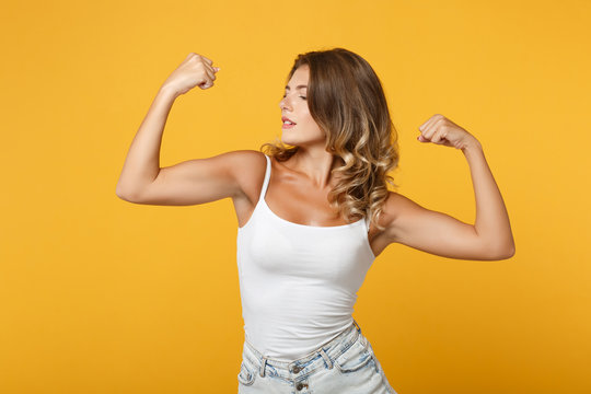 Strong young woman girl in light casual clothes posing isolated on yellow orange wall background studio portrait. People sincere emotions lifestyle concept. Mock up copy space. Showing biceps muscles.