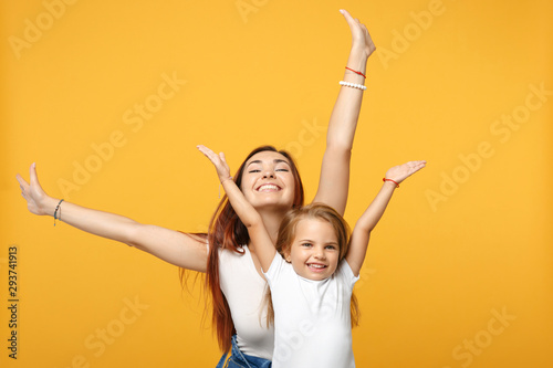 Woman in light clothes have fun with cute child baby girl 4-5 years old. Mommy little kid daughter isolated on yellow background studio portrait. Mother's Day love family parenthood childhood concept.