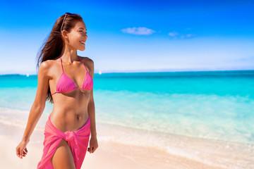 Fashion swimsuit bikini woman in hot pink swimwear walking on luxury travel vacation beach destination. Asian model relaxing.