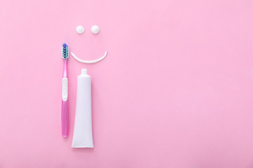 Tooth brush, paste and drawn smile on color background