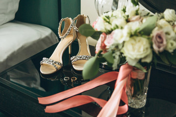 Beautiful wedding shoes and a pair of wedding rings nearby. Preparing for the wedding.