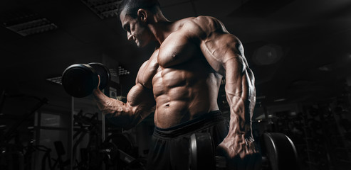 Muscular athletic bodybuilder fitness model training arms with dumbbells in gym. Concept sport photo of exercises in gym
