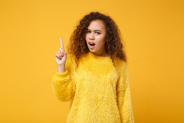 Concerned irritated young african american girl in fur sweater posing isolated on yellow orange background in studio. People lifestyle concept. Mock up copy space. Swearing, pointing index finger up.