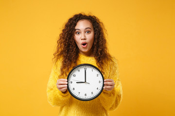 Amazed young african american girl in fur sweater posing isolated on yellow orange background, studio portrait. People lifestyle concept. Mock up copy space. Holding clock, keeping mouth wide open.