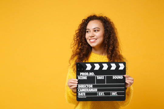 Smiling young african american girl in fur sweater posing isolated on yellow orange background in studio. People lifestyle concept. Mock up copy space. Holding classic black film making clapperboard.