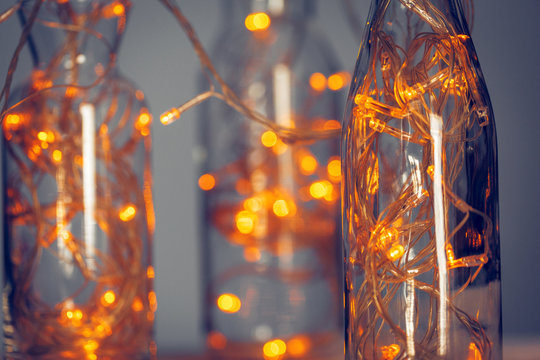 Lights garland in a glass bottle on a dark background