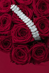 Luxury diamond jewelry bracelet and red roses flowers, love gift on Valentines Day and jewellery brand holiday background design