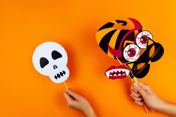 Female hands are holding paper photo props on orange background. White skull, cat mask, horns, vampire teeth, blood eyes, witch hat on canvas. Party accessories for celebrating happy halloween.