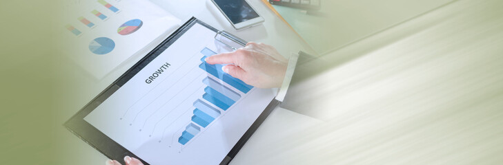 Businesswoman pointing her finger on a graph; panoramic banner