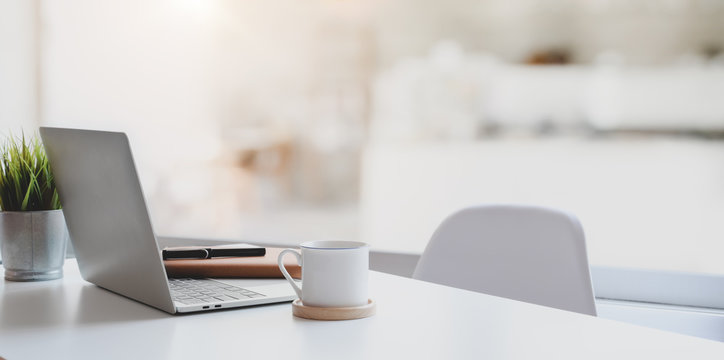 Modern workplace with laptop computer, coffee cup and office supplies