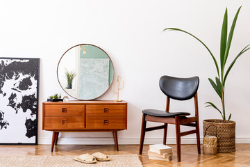 Stylish interior design of living room with wooden retro commode, chair, tropical plant in rattan pot, basket and elegant personal accessories. Mock up poster frame. Template. Home decor.