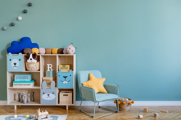 Scandinavian nursery room with wooden cabinet, mint armchair, natural teddy bears and plush animal...