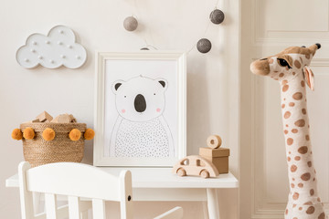 Modern and design scandinavian interior of kidroom with white desk, armachir, mock up poster frame, natural basket, toys, teddy bear, plush toys and cute children's accessories. Stylish home decor.