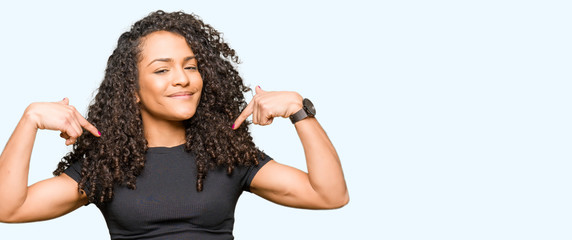 Young beautiful woman with curly hair looking confident with smile on face, pointing oneself with fingers proud and happy.