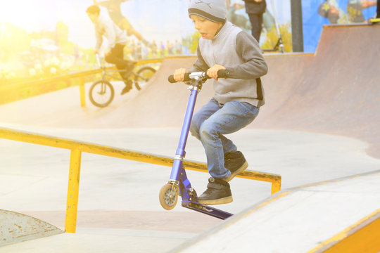 boy on kick scooter trains to ride and perform tricks like older guys in skate park
