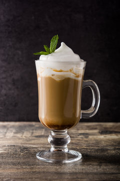 Peppermint coffee mocha for Christmas on wooden table and black background.