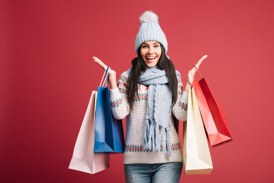 excited woman in winter sweater, scarf and hat holding shopping bags, isolated on red