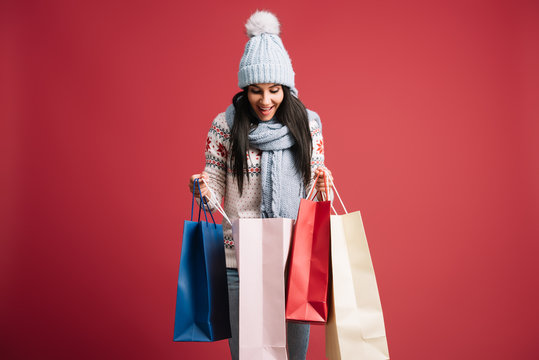 happy woman in winter sweater, scarf and hat looking into shopping bags, isolated on red