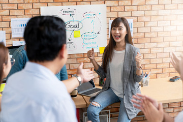 Happy asian creative woman or staff employee feeling enjoy with admires and praise by leadership or boss at small group meeting in creative office workplace. Woman feeling good with smiling face.