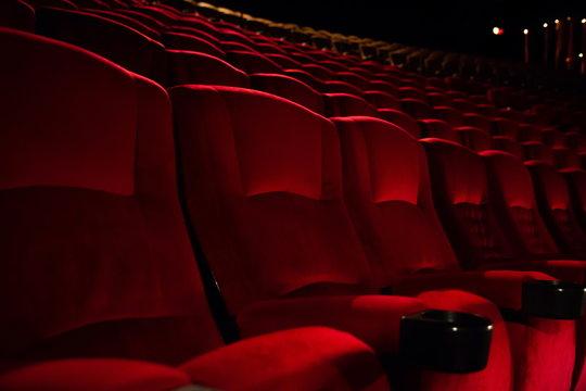 empty red velvet seats in cinema auditorium .