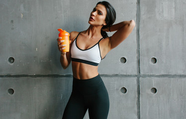 young brunette fitness woman with sportive nutrition shaker in brutal concrete gym