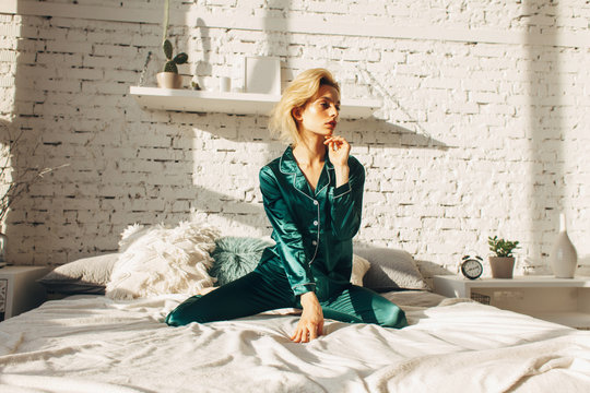 sensual fashionable woman in silk pajamas on bed in white bedroom, morning sunlight