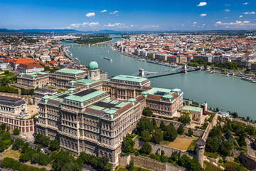 Budapest, Hungary - Aerial skyline view of Buda Castle Royal Palace on a bright summer day with Szechenyi Chain Bridge, River Danube and Parliament of Hungary at background taken with a drone
