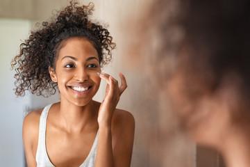 Young black woman applying skin cream