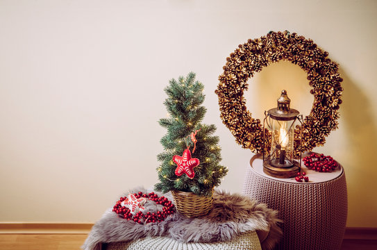 Small portable tabletop decorated Christmas tree on table, party lights illuminated, red felt fabric ornament. Light bulb lantern with pine cone wreath on background. Copy space for Christmas card.