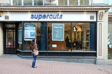 BIRMINGHAM, UK - APRIL 19: Woman watches Supercuts window on April 19, 2013 in Birmingham, UK. Supercuts is a cheap haircut salon franchise with 180+ salons in the UK and 2000+ worldwide.