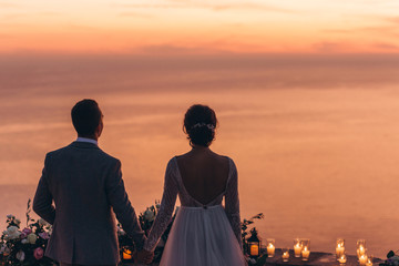 The bride and groom together admire a beautiful red sunset. Fototapete