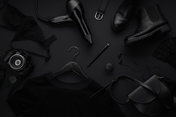 Black monochromatic flatlay on black background. Clothes, accessories and beauty equipment. Black friday sale concept