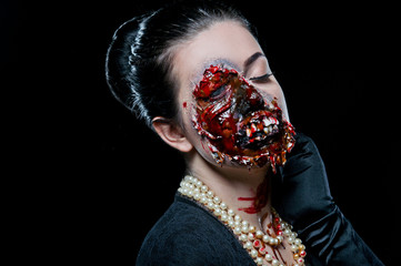 Woman with horror make up in the studio on a black background. Halloween make up. Zombie. Fototapete