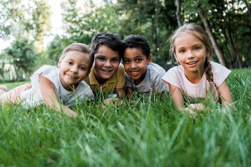 selective focus of cute multicultural children smiling while lying on grass