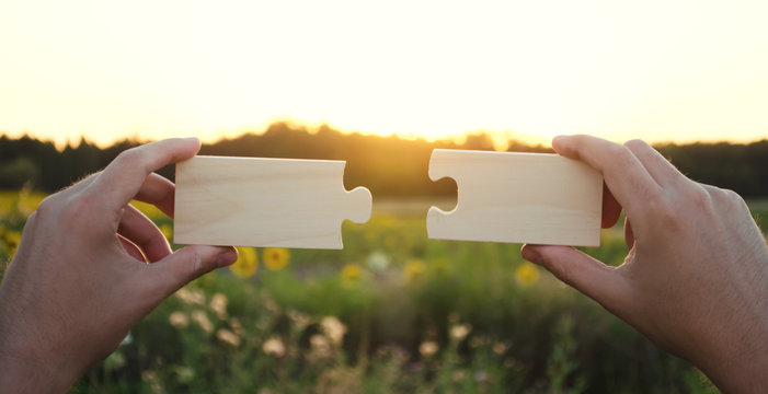 A man collects wooden puzzles at sunset. Concept of success, business solutions. Strategy and goal achievement. Making the right decision. Connection and partnership. Selective focus