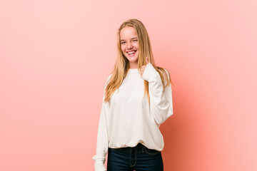 Young blonde teenager woman smiling and raising thumb up
