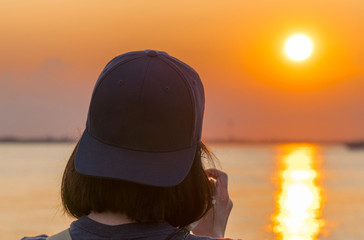 Female photographer takes picutres of a beautiful orange sunset over the water wearing backwards blue hat. Over the shoulder composition.