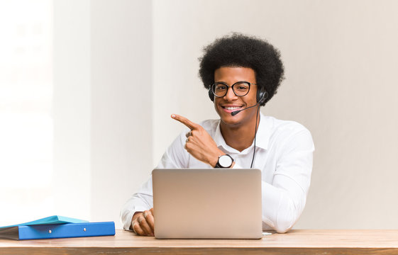 Young telemarketer black man smiling and pointing to the side