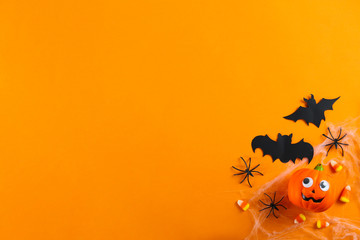 Halloween themed flat lay composition with decorative jack-o-lantern pumpkins, on paper textured background with a lot of space for text. Close up, top view.