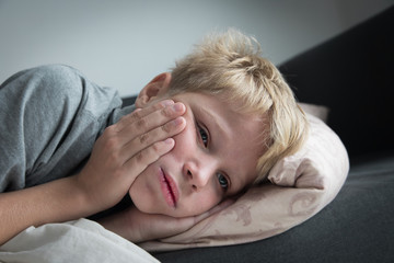 Sick child with fever at home, kid with toothache
