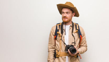 Young redhead explorer man smiling confident and crossing arms, looking up. Holding a camera.